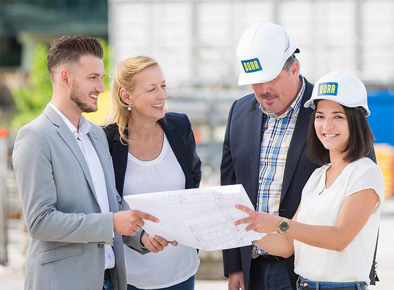Photo: four smiling people in casual business outfits, two wearing a work helmet, all looking at a construction plan